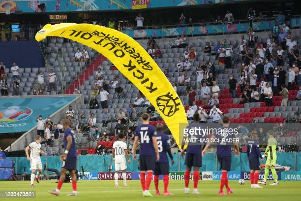 Paraglider sporting a message from environmental action group Greenpeace lands on the pitch during the UEFA EURO 2020 Group F football match between...