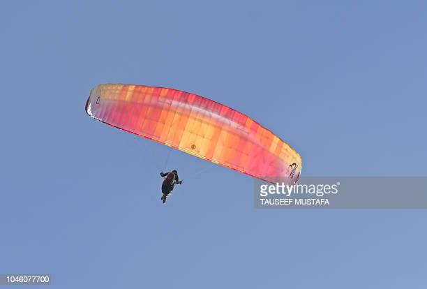 A paraglider takes a flight as riders compete in the 14th edition of the Hero MTB Himalaya mountain bike race in the northern Indian state of...