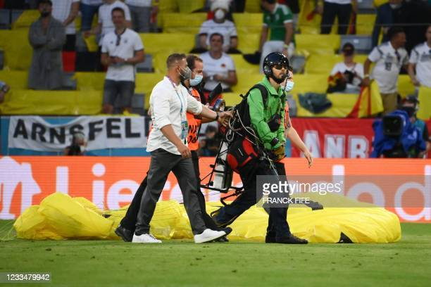 Paraglider, who flew inside the stadium sporting a message from environmental action group Greenpeace, is escorted by security after landing on the...