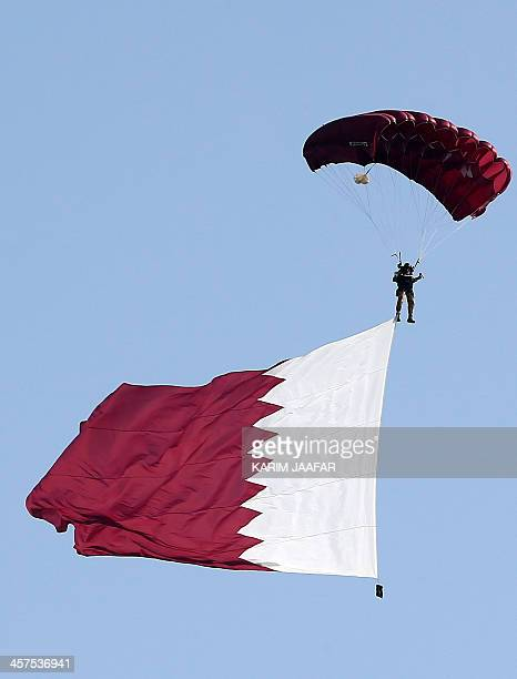 A paraglider with the national flag attached to his leg flies over the capital during the Gulf emirate's National Day celebrations in Doha on...