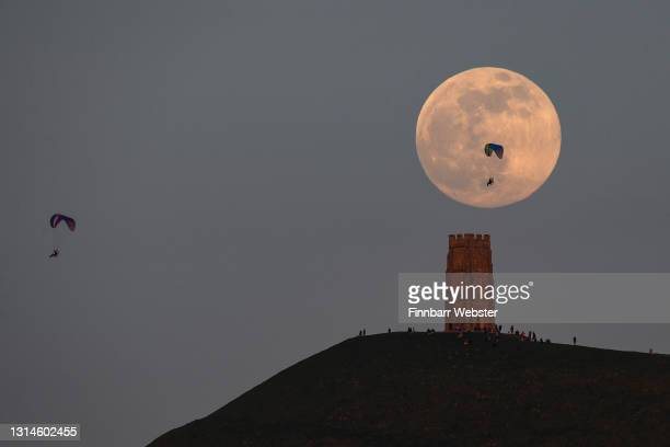Paragliders are seen as the full moon rises behind Glastonbury Tor on April 26, 2021 in Glastonbury, England. The pink supermoon will reach peak size...