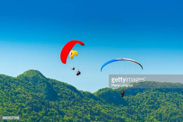 paragliders flying above the village of talloires and lake annecy - haute-savoie - france - lake annecy stock photos and pictures