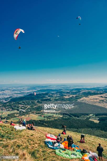 paragliders on puy de dome, auvergne, france - auvergne rhône alpes stock pictures, royalty-free photos & images