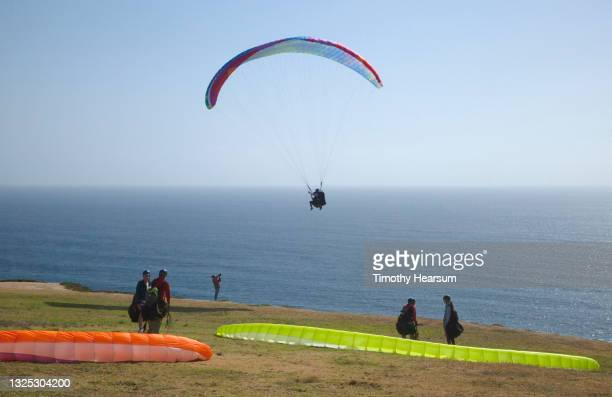 paragliders preparing to take off and join one other already in the air; ocean and blue sky beyond - timothy hearsum fotografías e imágenes de stock