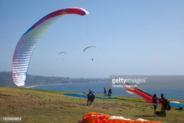 paragliders preparing to take off and join two others already in the air; ocean, coastline and blue sky beyond - timothy hearsum ストックフォトと画像