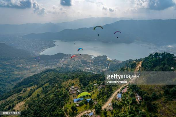 paragliders sail over mountains and lake on a stormy day - pokhara stock pictures, royalty-free photos & images