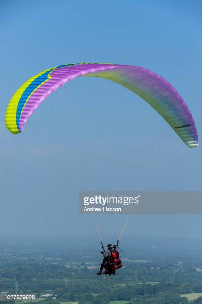 Paragliders take advantage of the fine conditions and northwesterly winds as they fly from the Devil's Dyke over Sussex Weald on September 6 2018...