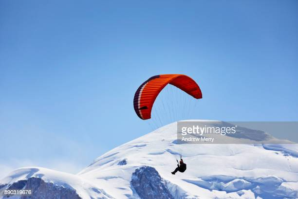 Paragliding at high altitude. Flying past the famous snow-capped Mont Blanc summit (4,810 m) which is the highest mountain in western Europe.