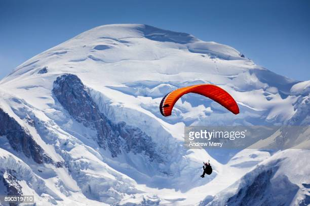 paragliding at high altitude. flying past the famous snow-capped mont blanc summit (4,810 m) which is the highest mountain in western europe. - mont blanc massif stock photos and pictures