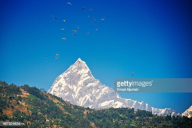 paragliding in pokhara, nepal with mount fishtail in the background - pokhara stock pictures, royalty-free photos & images