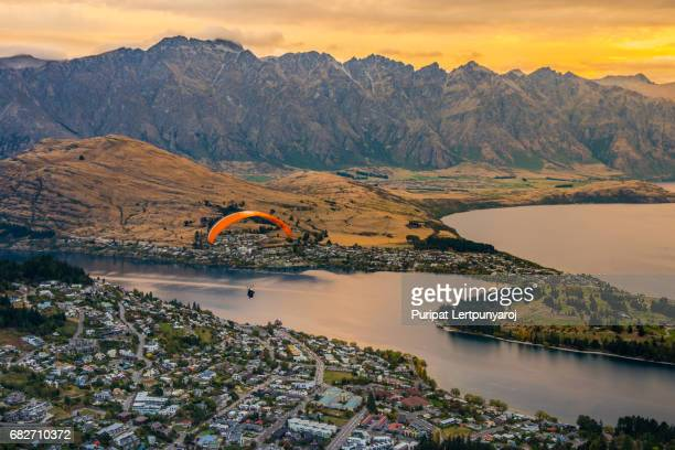 paragliding over queenstown and lake wakaitipu from viewpoint at queenstown skyline, new zealand - queenstown stock pictures, royalty-free photos & images