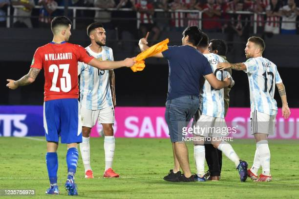 Paraguayan fan enters to the field to take a selfie with Argentina's Lionel Messi during the South American qualification football match for the FIFA...