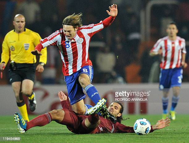 Paraguayan midfielder Edgar Barreto is marked by Venezuelan defender Oswaldo Vizcarrondo during their 2011 Copa America semifinal football match held...
