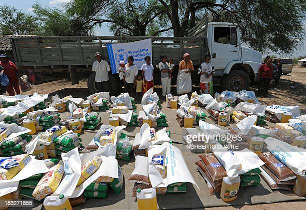 Paraguayan natives from the Comunidad Esperanza in Chaco 240 km north of Asuncion stand behind supplies they received from the UN World Food...