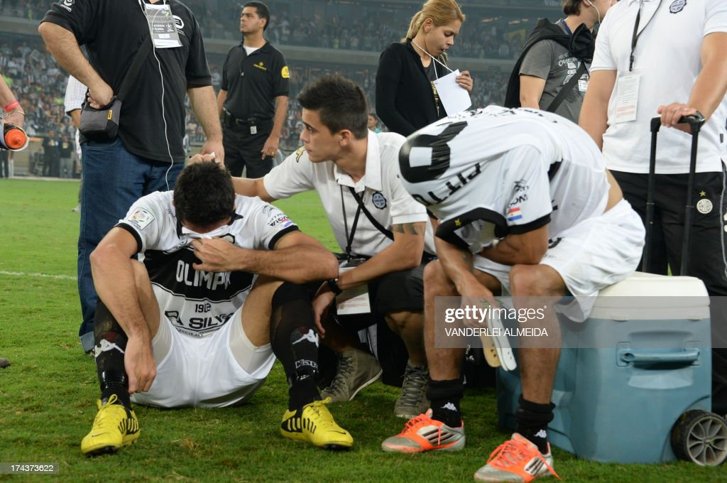 Paraguayan Olimpia's players react in dejection after losing their Libertadores Cup second leg final football match shoot-out against Brazilian Atletico Mineiro at the Mineirao stadium in Belo Horizonte, Brazil on July 24, 2013. Atletico Mineiro won by 4-3 after a penalty shoot-out.