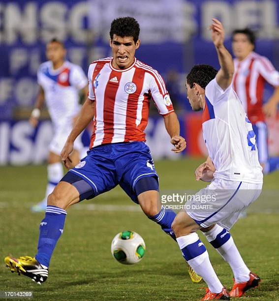 Paraguayan player Eugenio Mena and Chile's forward Cristian Riveros vie for the ball during a Brazil 2014 FIFA World Cup South American qualifier...