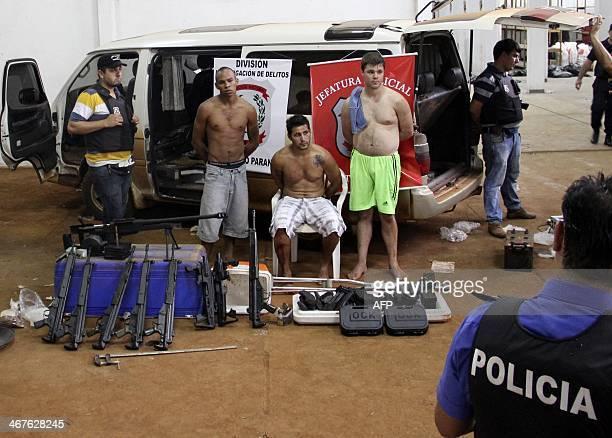 Paraguayan policemen stand next to Brazilian nationals Roberto Torres Gonzalez Antonio Cesar Ibarra and Luis Fernando Cabral and weaponsassault...