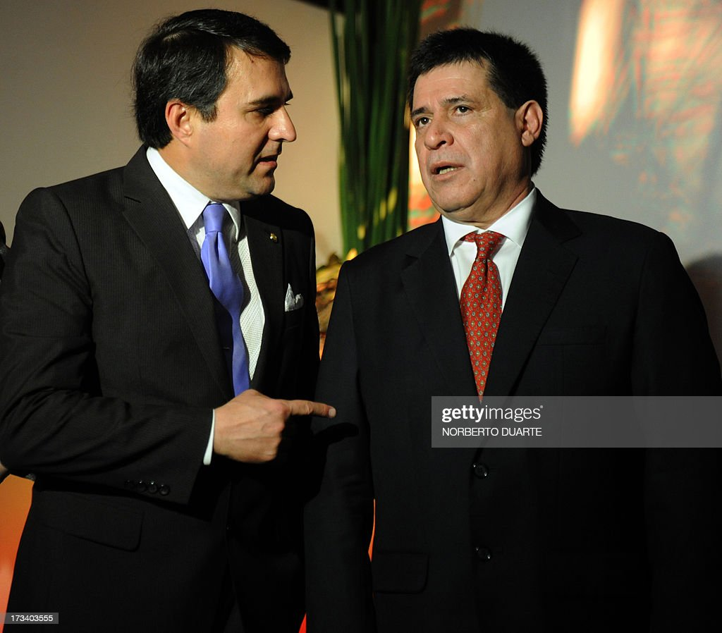 Paraguayan President Federico Franco (L) talks with President-elect Horacio Cartes during the opening of an industial and agricultural fair in Mariano Roque Alonso, Paraguay, on July 13, 2013. On Friday the Mercosur trade bloc meeting in Montevideo agreed to reinstate Paraguay's membership once rightwing tycoon Horacio Cartes, elected president in April, takes office on August 15. Cartes however appeared to reject the offer saying that Venezuela's admission to the group did not follow the proper legal procedure. Argentina, Brazil and Uruguay suspended Paraguay from Mercosur after Paraguay's Congress impeached leftist president Fernando Lugo and removed from office in June 2012. With Paraguay gone, Argentina, Brazil and Uruguay admitted leftist Venezuela as a Mercosur member. AFP PHOTO / Norberto DUARTE