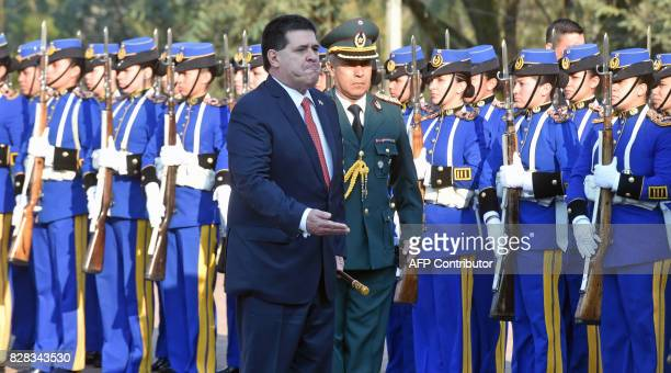 Paraguayan President Horacio Cartes reviews troops as he arrives at the appointing ceremony of Admiral Hugo Milciades Scolari Pagliaro as new...