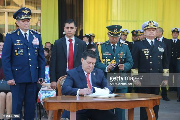 Paraguayan President Horacio Cartes signs a document appointing Admiral Hugo Milciades Scolari Pagliaro as new Commander in Chief of the Paraguayan...