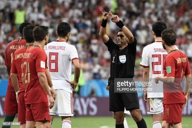 Paraguayan referee Enrique Caceres gestures for VAR during the Russia 2018 World Cup Group B football match between Iran and Portugal at the Mordovia...