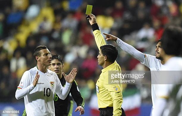 Paraguayan referee Enrique Caceres shows a yellow card to Bolivia's midfielder Pablo Escobar during the Copa America football match against Mexico in...