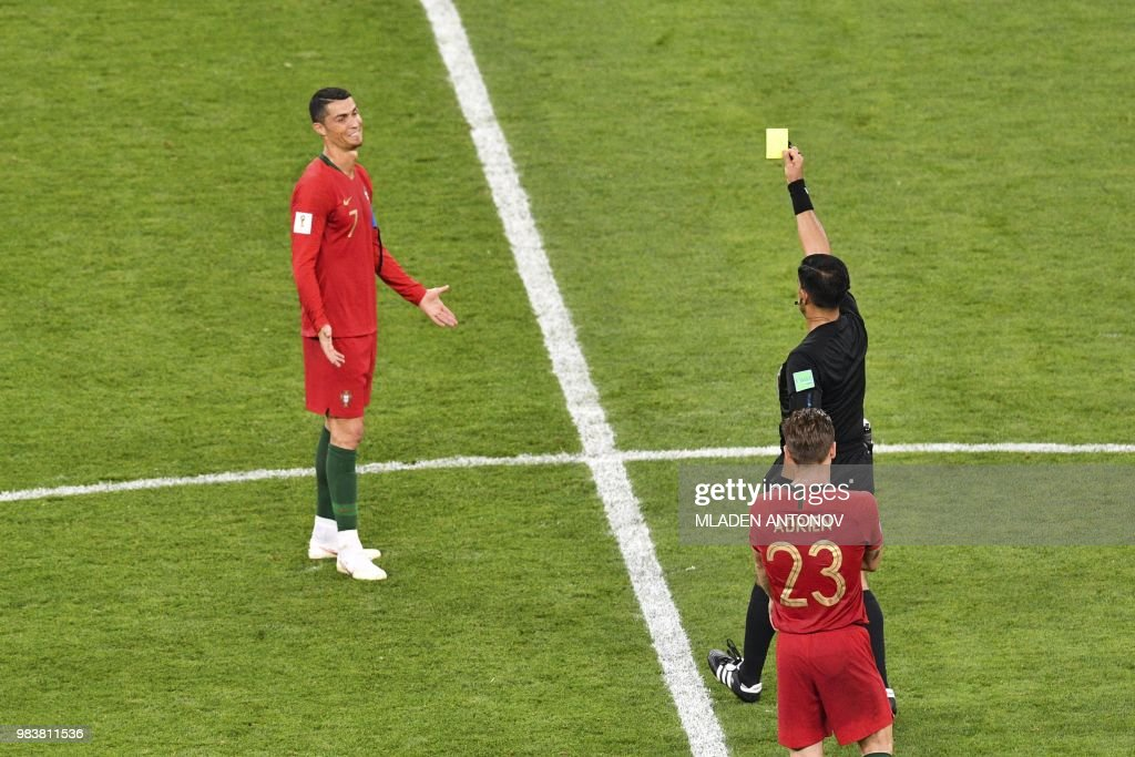 TOPSHOT - Paraguayan referee Enrique Caceres shows the yellow card to Portugal's forward Cristiano Ronaldo during the Russia 2018 World Cup Group B football match between Iran and Portugal at the Mordovia Arena in Saransk on June 25, 2018. (Photo by Mladen ANTONOV / AFP) / RESTRICTED