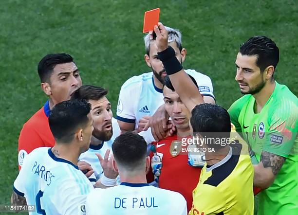Paraguayan referee Mario Diaz de Vivar shows the red card to Argentina's Lionel Messi and Chile's Gary Medel during the Copa America football...