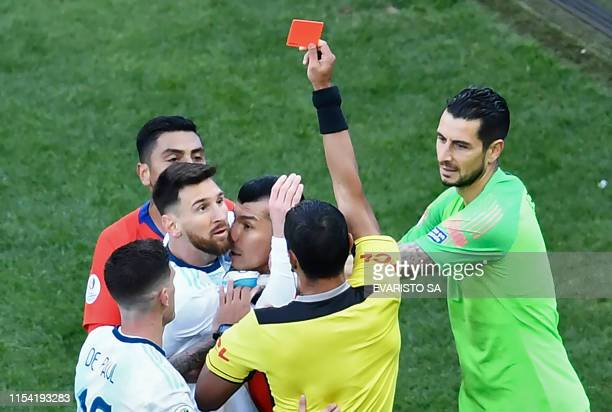 TOPSHOT Paraguayan referee Mario Diaz de Vivar shows the red card to Argentina's Lionel Messi and Chile's Gary Medel as they have a physical...