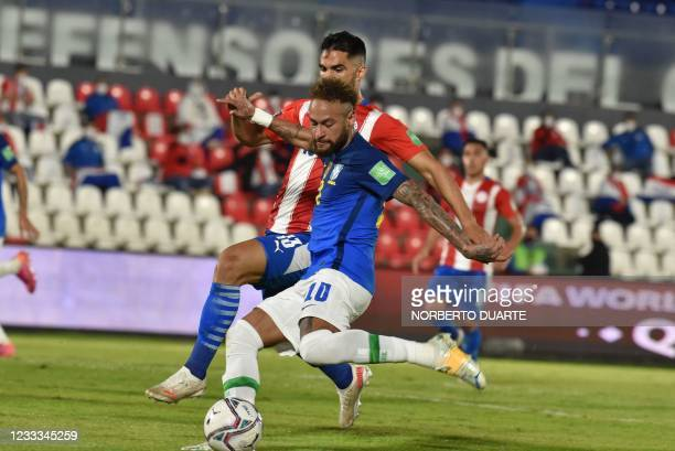 Paraguay's Alberto Espinola and Brazil's Neymar vie for the ball during their South American qualification football match for the FIFA World Cup...