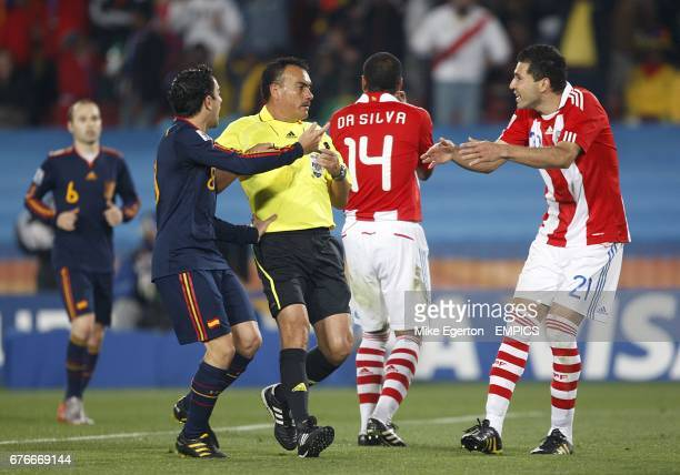 Paraguay's Antolin Alcaraz argues with referee Carlos Batres prior to being booked