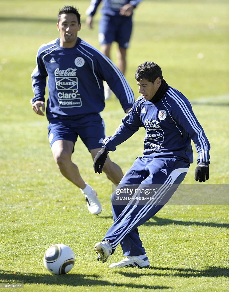 Paraguay's defender Carlos Bonet (R) strikes the ball next to teammate forward Lucas Barrios (L) during a training session at Michaelhouse school in Balgowan on June 16, 2010 ahead their second 2010 World Cup Group F football match against Slovakia on June 20 at Free State stadium in Bloemfonstein.