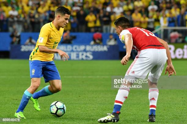 Paraguay's defender Junior Alonso vies for the ball with Brazil's midfielder Philippe Coutinho during their 2018 FIFA World Cup qualifier football...