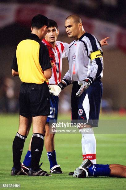 Paraguay's Denis Caniza and Jose Luis Chilavert complain to referee Masayoshi Okada after a teammate was fouled