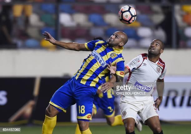 Paraguays Deportivo Capiata player Dioniso Perez Mambreani vies for the ball with Perus Universitario player John Galliquio during their firstround...