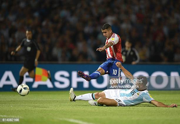 TOPSHOT Paraguay's Derlis Gonzalez kicks to score under the mark of Argentina's Martin Demichelis during the Russia 2018 FIFA World Cup qualifier...