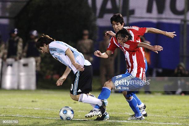 Paraguay's Eduardo Ledesma vies for the ball with Lionel Messi of Argentina during their 2010 FIFA World Cup qualifier at the Defensores del Chaco...