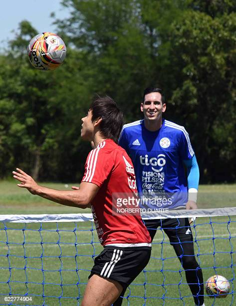 Paraguay's footballer Oscar Romero and goalkeeper Roberto Fernandez take part in a training session at the Albiroga Complex training centre in Ypane...