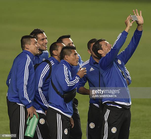 Paraguay's forward Nelson Valdez takes a selfie with teammates during the field recognition at Alcaldesa Ester Roa Rebolledo stadium in Concepcion,...