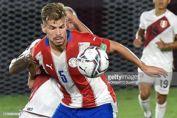 Paraguay's Gaston Gimenez eyes the ball during the 2022 FIFA World Cup South American qualifier football match against Peru at the Defensores del...