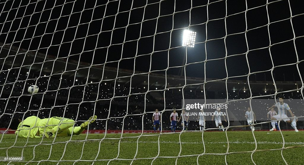 Paraguay's goalkeeper Justo Villar (L) dives to stop a penalty kicked by Argentina's forward Sergio Aguero during their Russia 2018 World Cup football qualifier match in Cordoba, Argentina, on October 11, 2016. Paraguay won 1-0. / AFP / JUAN