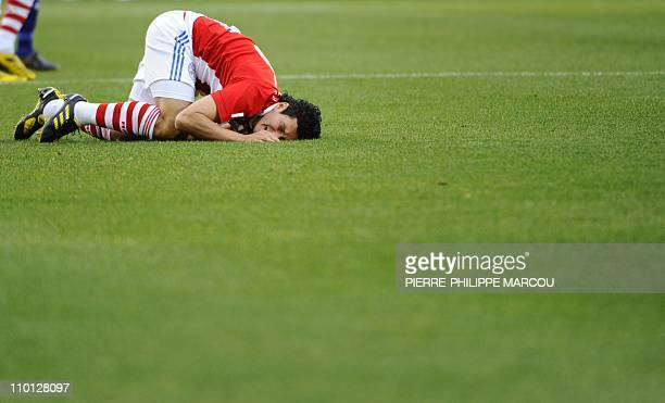 Paraguay's midfielder Cristian Riveros reacts in pain after falling during the 2010 World Cup round of 16 football match between Paraguay and Japan...