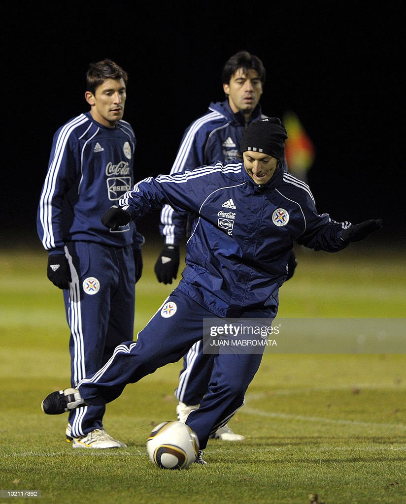 Paraguay's midfielder Edgar Barreto (front) strikes a ball next to forward Edgar Benitez (L) and defender Julio Cesar Caceres during a training session at Michaelhouse school in Balgowan on June 15, 2010 a day after their first match against Italy ended 1-1 and ahead their second 2010 World Cup Group F football match against Slovakia on June 20 at Free State stadium in Bloemfonstein.