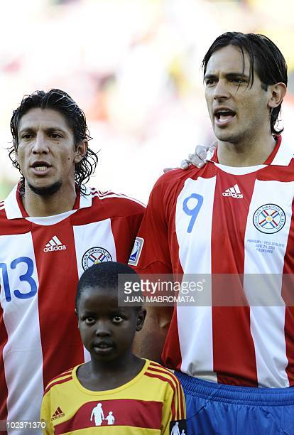 Paraguay's midfielder Enrique Vera and Paraguay's striker Roque Santa Cruz sing their national anthem prior to the start of the Group F first round...