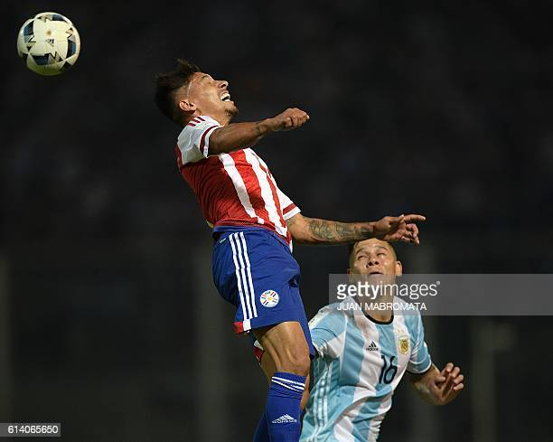 Paraguay's midfielder Hernan Perez heads the ball next to Argentina's Marcos Rojo during their Russia 2018 World Cup football qualifier match in...