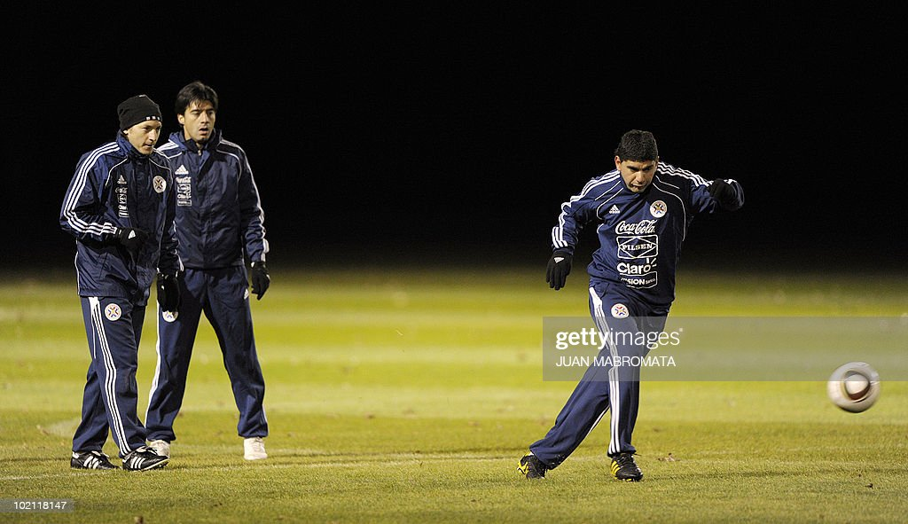 Paraguay's midfielder Nestor Ortigoza (R) jogs with a ball next to teammates midfielder Edgar Barreto (R) and defender Julio Cesar Caceres during a training session at Michaelhouse school in Balgowan on June 15, 2010. The 2010 World Cup hosted by South Africa continues through July 11.