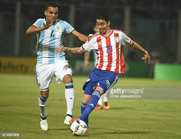 Paraguay's Miguel Almiron vies for the ball with Argentina's Gabriel Mercado during their Russia 2018 World Cup football qualifier match in Cordoba...