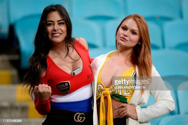 Paraguay's model Larissa Riquelme poses for pictures with a Brazilian fan before the Copa America football tournament quarterfinal match between...