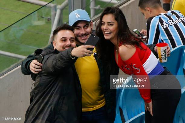 Paraguay's model Larissa Riquelme poses with football fans before the Copa America football tournament quarterfinal match between Paraguay and Brazil...