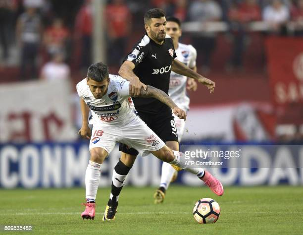 Paraguay's Nacional forward Jose Nunez vies for the ball with Argentina's Independiente forward Emmanuel Gigliotti during their Copa Sudamericana...